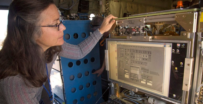 Woman scientist checks observing equipment aboard an NCAR research aircraft