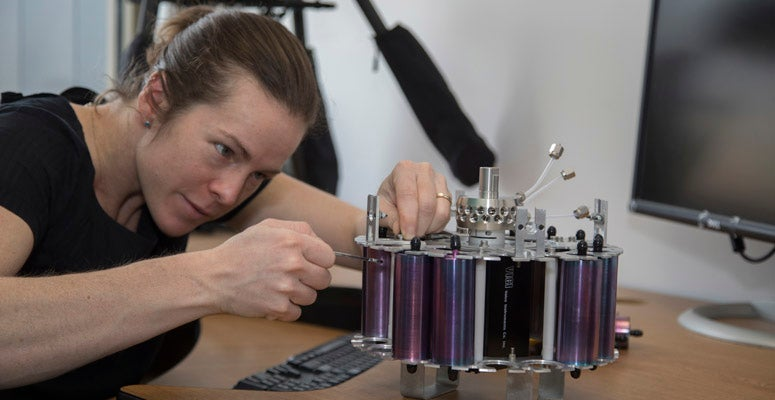 A scientist works on an instrument