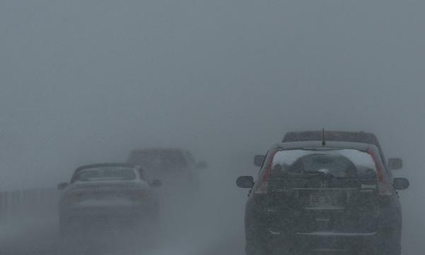 Vehicles travel through fog on winter road